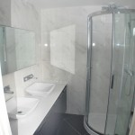 bathroom with shower and double sink