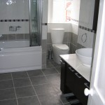 stylish modern bathrrom with white bath, toliet and sink